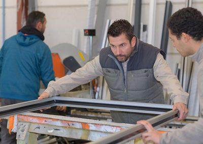 men-working-at-plastic-door-and-window-factory-P7WYT83
