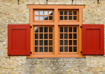 old-red-wooden-window-on-brock-wall-PEGRKBP